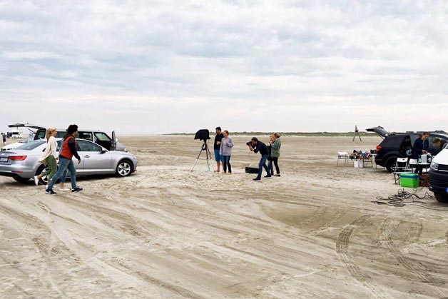 Das Team der Bild- und Videoproduktion bei Aufnahmen am Strand - Windrich & Sörgel